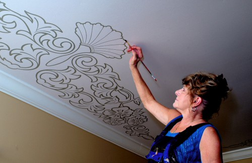 Mimi works on a ceiling